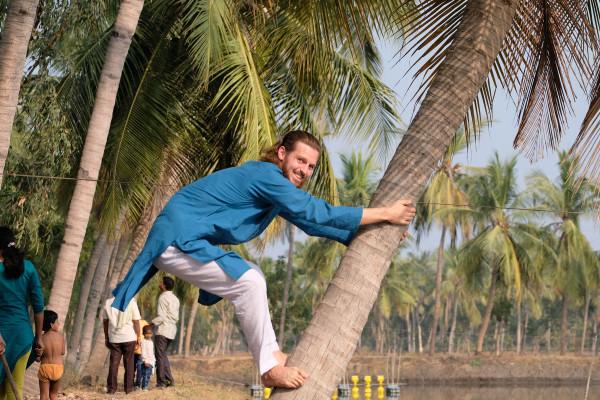 Schwieriger als gedacht: An der indischen Ostküste versucht Sebastian auf eine Kokospalme zu klettern (Retrieved from www.eins2frei.com)